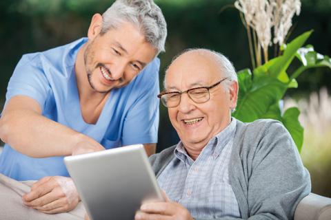 Mann zeigt Senior etwas am Tablet